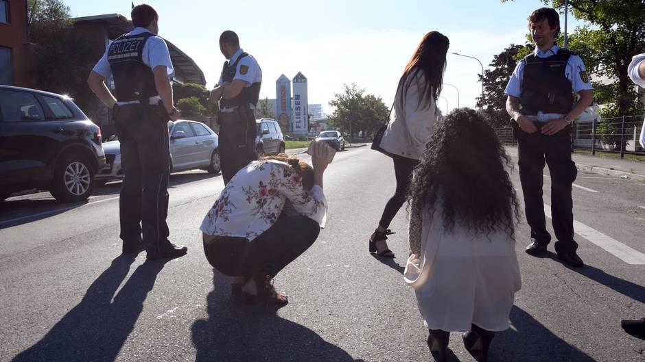 Polizisten und Zeugen stehen am vor dem Club in Konstanz, in dem die Schüsse gefallen sind