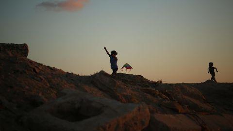 Urlaub: Zwei Kinder spielen mit einem Drachen am Strand