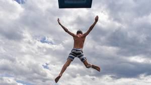 Ein Junge springt vom Drei-Meter-Brett - kommt jetzt der Sommer?