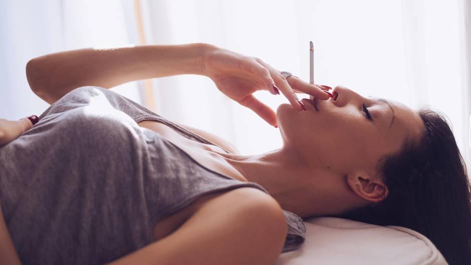 Eine Frau liegt im Bett und raucht