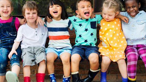 Kinder sitzen Arm in Arm auf einer Bank