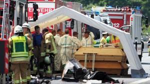 Feuerwehr und Polizei steht am Unfallort. Mehrere Särge werden unter einem Zelt bereitgestellt.