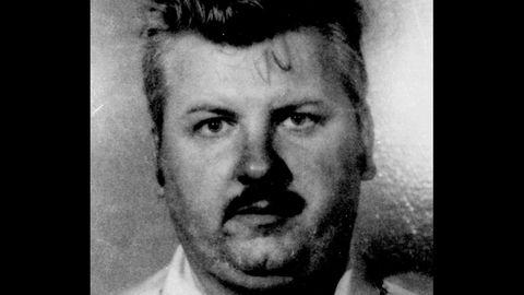 Ein Schwarz-weiß-Foto zeigt einen Mann mit rundlichem Gesicht und Schnauzbart: Serienmörder John Wayne Gacy