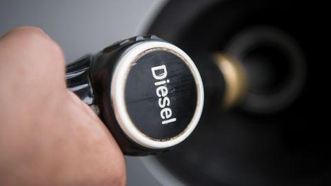 """Ein Hand hält einen Tankrüssel mit der Aufschrift """"Diesel"""" in den Tankstutzen eines silbergrauen Autos"""