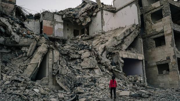 Nur noch Schutt und Beton: Ein Mädchen läuft über die Reste eines Wohnhauses, das bei einem Luftangriff zerstört wurde