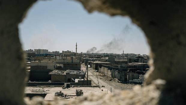 Der Blick durch ein zerstörtes Haus auf die Altstadt von Raqqa. In der Ferne steigt Rauch von einem Bombenangriff auf