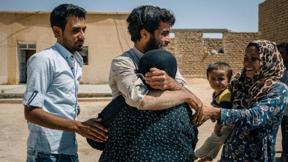 Wiedersehen nach der Flucht: Um Ahmed wird von einem ihrer Söhne in den Arm genommen, als sie das Dorf erreicht, das der Familie Sicherheit verspricht