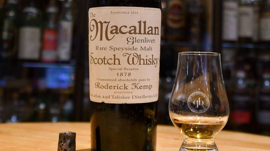 Eine Flasche Macallan Scotch Whisky von 1878 steht neben einem Whisky-Glas