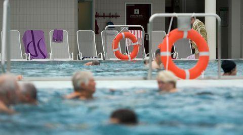 Mehrere ältere Personen schwimmen in einem Hallenbad.