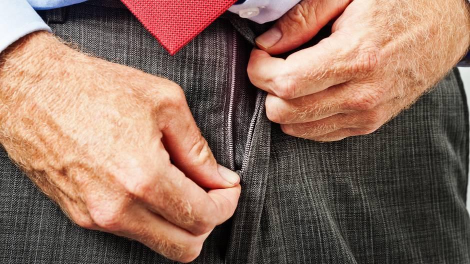 Ein Mann öffnet seine Hose