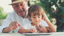 Großvater und Enkel schauen auf ein Tablet