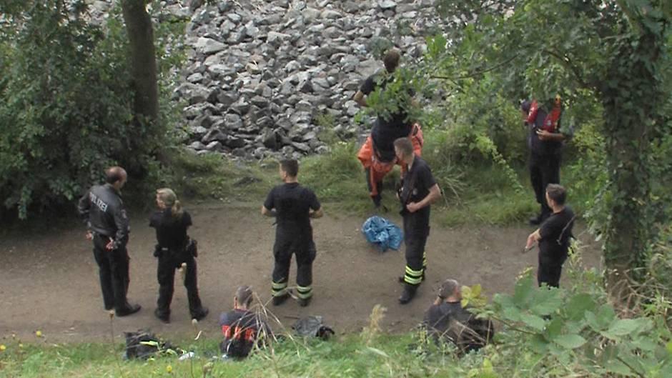 Polizisten und Feuerwehrleute bewachen einen blauen Sack, nachdem ein Angler Leichenteile am Elbufer gefunden hatte