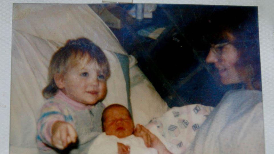 Der Junge am Tag nach seiner Geburt mit der Halbschwester und der Mutter
