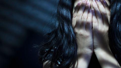 Dunkelhaarige Frau bedeckt ihr Gesicht mit beiden Händen