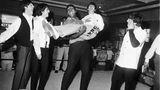 """Als er Anfang 1964 die Beatles in Miami traf, hieß der spätere Boxchampion Muhammad Ali noch Cassius Clay und stand kurz vor seinem ersten großen Kampf gegen Sonny Liston. Für die Kamera von Harry Benson machten alle ein paar Faxen - und Ali nahm Ringo Starr buchstäblich auf den Arm. Der Fotograf sagt über diese Zusammenkunft: """"Ich hatte natürlich keinen blassen Schimmer, dass ich zwei der größten Ikonen des 20. Jahrhunderts zusammen fotografierte."""""""