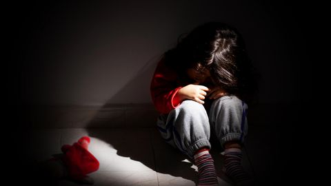 Ein Mädchen sitzt traurig im dunklen Zimmer