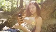 Eine junge Frau hat ihr Smartphone in der Hand und sitzt im Wald