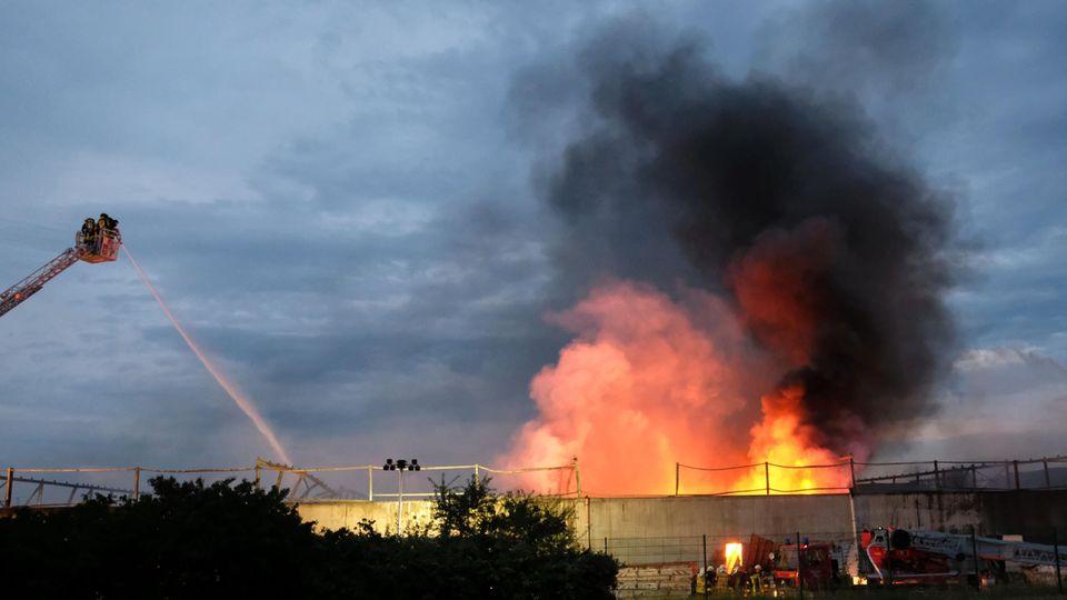 Feuerwehrleute löschen ein Feuer auf einem Industriegelände in Bitterfeld-Wolfen