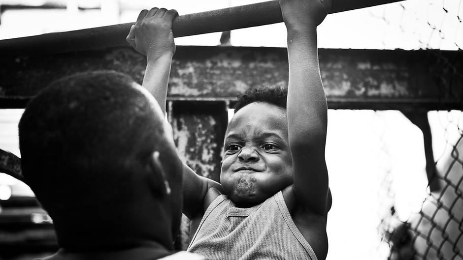 """""""Dieser Junge ist etwa sechs Jahre alt und strengt sich bei den Klimmzügen sehr an. Mit Hilfe des Trainers schafft er es, die Übung zu meistern. Der Gesichtsausdruck dabei ist von Anstrengung gezeichnet."""""""
