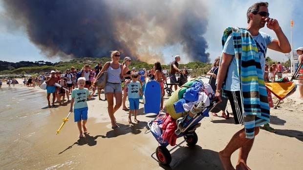 Bormes-les-Mimosas, Département Var, Frankreich: Touristen fliehen über den Strand vor den nahenden Flammen