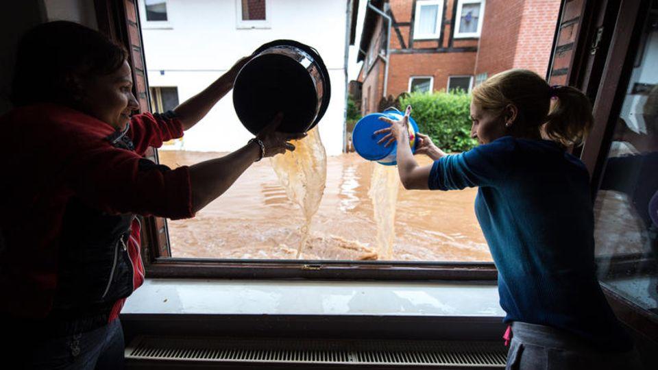 Rhüden, Harz, Niedersachsen: Mit Eimern schöpfen Frauen das Wasser aus ihrer Wohnung. 200 Häuser sind hier von den Überschwemmungen betroffen