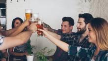 Junge Menschen stoßen mit Bier an