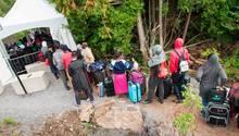 Vor einer improvisierten Kontrollstelle stehen Flüchtlinge mit Gepäck Schlange, um von den USA nach Kanada zu gelangen