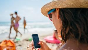 Nur mal schnell die Mails checken: Eine Frau am Strand mit Handy