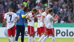 Spieler des Hamburger SV stehen nach dem Erstrunden-Aus im DFB-Pokal gegen den VfL Osnbrück mit gesenkten Köpfen auf dem Rasen