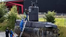 Auf Holzböcken steht ein U-Boot an Land. Aus dem Turm schaut ein Mann mit Atemschutz, ein zweiter klettert eine Leiter empor.