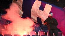 Vermummter Hooligan vor brennendem Banner von Hertha BSC auf den Rängen des Ostsee-Stadions in Berlin