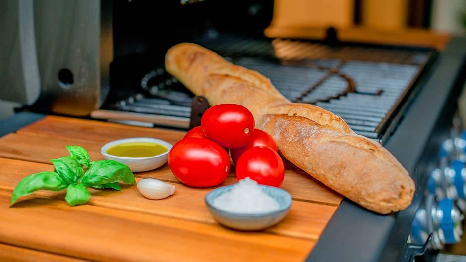 Was Sie für Bruschetta vom Grill brauchen? Ein Ciabatta oder Baguette, Fleischtomaten, eine Knoblauchzehe, Basilikum, Olivenöl und etwas Salz.