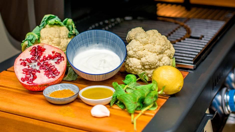 Was Sie für den orientalischen Blumenkohl brauchen? Blumenkohl, Joghurt, Granatapfel, Ras-El-Hanout, Minze, Zitrone, Knoblauch und Olivenöl.