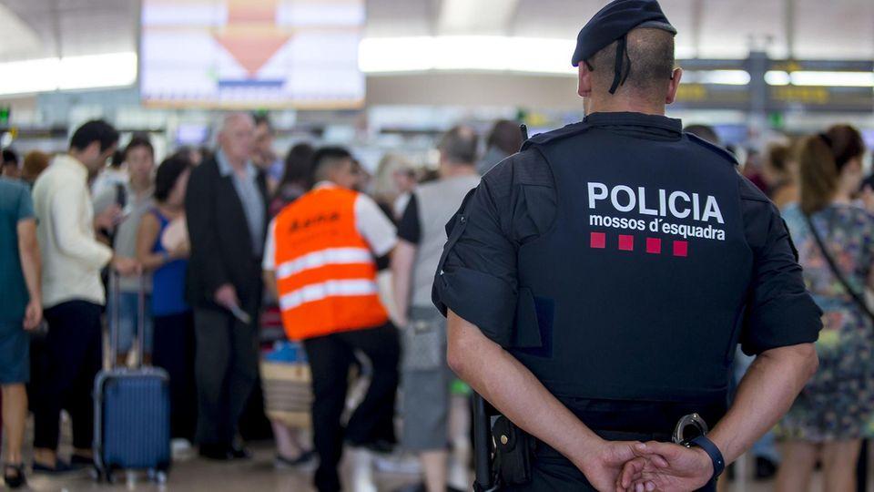 Ein Polizist steht während des Streiks am Flughafen in Barcelona, Spanien