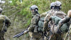 Elite-Soldaten der Bundeswehr in Tarnkleidung und mit Maschinengewehr bei einer Übung