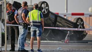 Terror in Barcelona und Cambrils: Polizisten stehen in Cambrils neben einem auf dem Dach liegenden Auto
