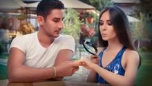 Eine Frau schaut mit einer Lupe auf ihren Verlobungsring