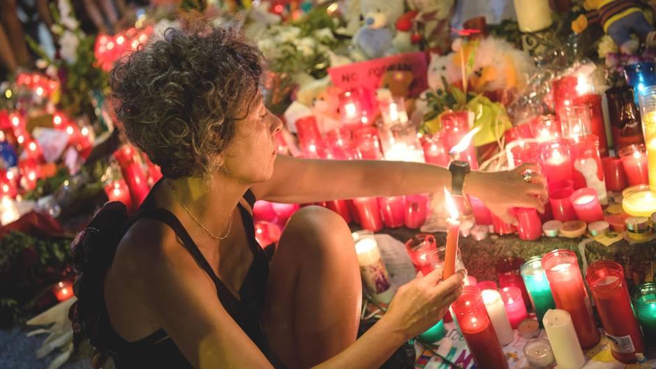 Eine Frau zündet am Anschlagsort auf der Flaniermeile Las Ramblas in Barcelona erloschene Kerzen wieder an