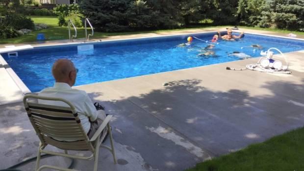 Keith Davison blickt auf seinen Pool, in dem Kinder schwimmen