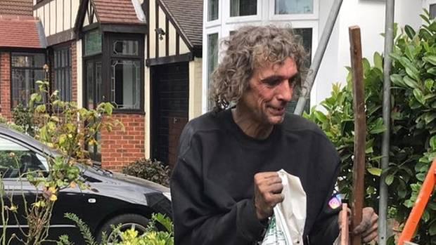 Der obdachlose John räumt mit einem Lächeln im Gesicht einen Garten auf