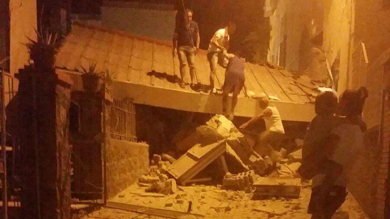 Erdbeben auf Ischia in Italien: Eine Frau steht mit einem Kleinkind im Arm vor einem eingestürzten Gebäude