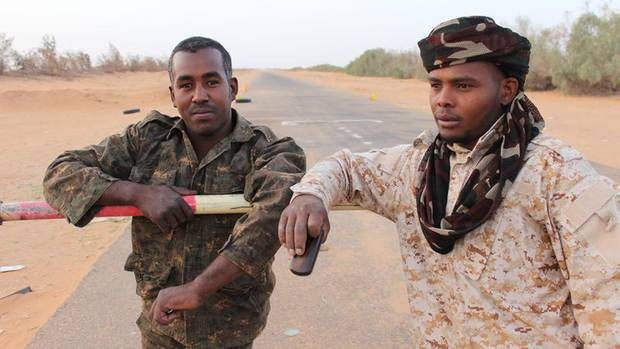 Issa Hassan (l.) am Schlagbaum der Grenze Niger zu Libyen. Er und seine Männer vom Stamm der Tubu patrouillieren in dem unsicheren Gebiet