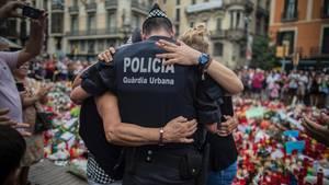 Ein Polizist umarmt an der Gedenkstätte für die Opfer des Anschlags in Barcelona einen Jungen und dessen Familie
