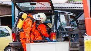In speziellen Chemieschutzanzügen holen Feuerwehrleute in Schlangenbad das Wasserstoffperoxidaus dem Tank eines Lada