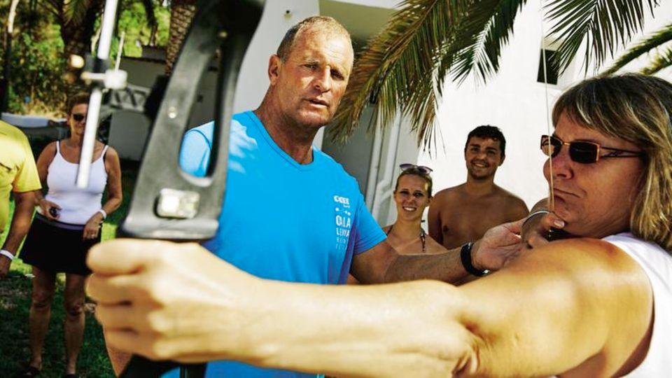 """Mission Spaß: Puch zeigt einer Urlauberin die richtige Haltung beim Bogenschießen, """"dem perfekten Sport für alle, die keine Lust auf Sport haben"""""""