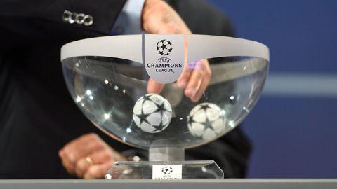 Eine Hand greift in einen durchsichtigen Lostopf mit Champions League Logo. In der Schale liegen noch zwei Kugeln.