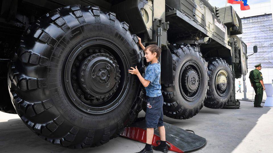 Atomwaffen zum Anfassen - ein Junge spielt mit den Reifen des Transporters einer Topol-M Interkontinentalrakete.