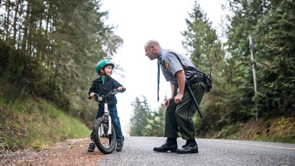 Polizist ermahnt Kind auf einem Fahrrad