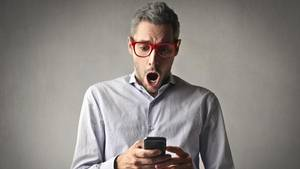Ein Mann schaut schockiert auf sein Smartphone