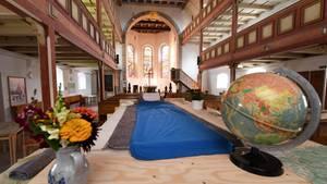 Ein Bett steht in der Michaeliskirche in Neustadt am Rennsteig in Thüringen: Radfahrer, Wanderer und interessierte Touristen erhalten hier eine Übernachtungsmöglichkeit für bis zu drei Personen im Innenraum der Kirche.